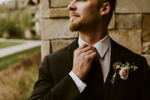 Groom straightening black tie and wearing boutonniere