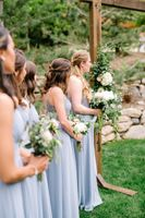 Bridesmaids line in ceremony with bouquets.