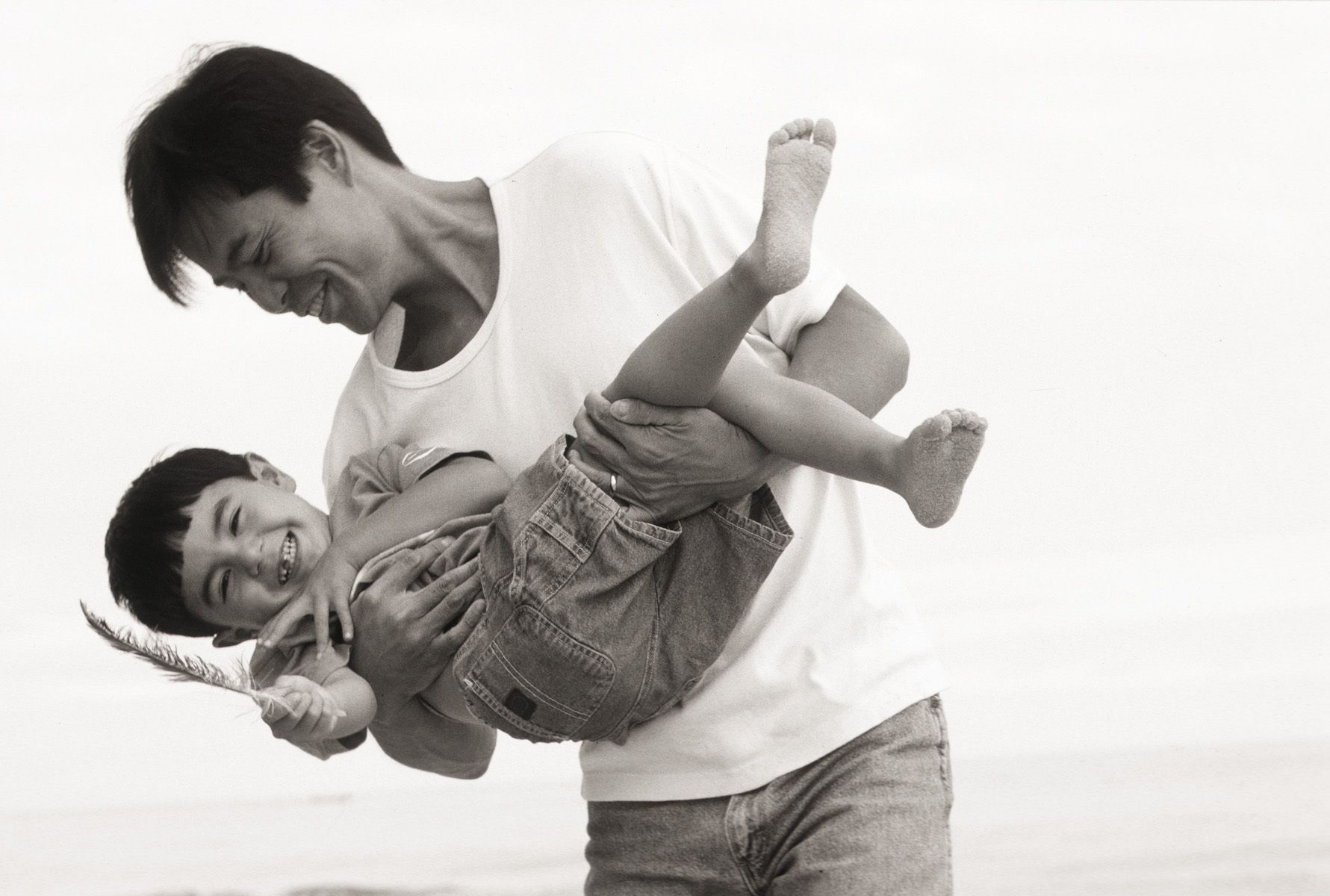 Asian father and son playing on the beach