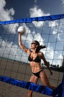 Young fit woman playing beach vollyball