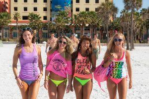Four girls in bikinis walking on the beach