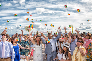 Wedding celebration throwing beach balls in the air
