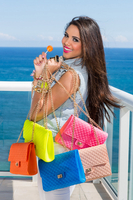 Young  woman on deck of yacht with display of colorful purses