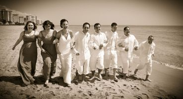 Wedding party running on the beach