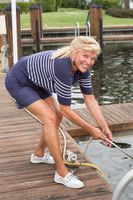 Woman pulling the boat rope on the dock