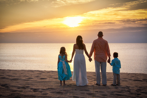 Wedding day on the beach at sunrise with daughter and son.