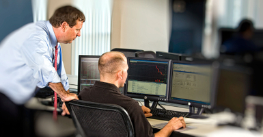 Businessmen consulting information on multiple computer screens