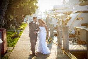Bride and Groom walking  on the dock in  Marina