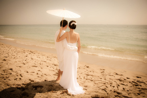 Wedding Couple on beach with Parasol