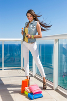Model  on balcony with pile of purse's