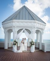 Newlyweds posing in Gazebo overlooking ocean