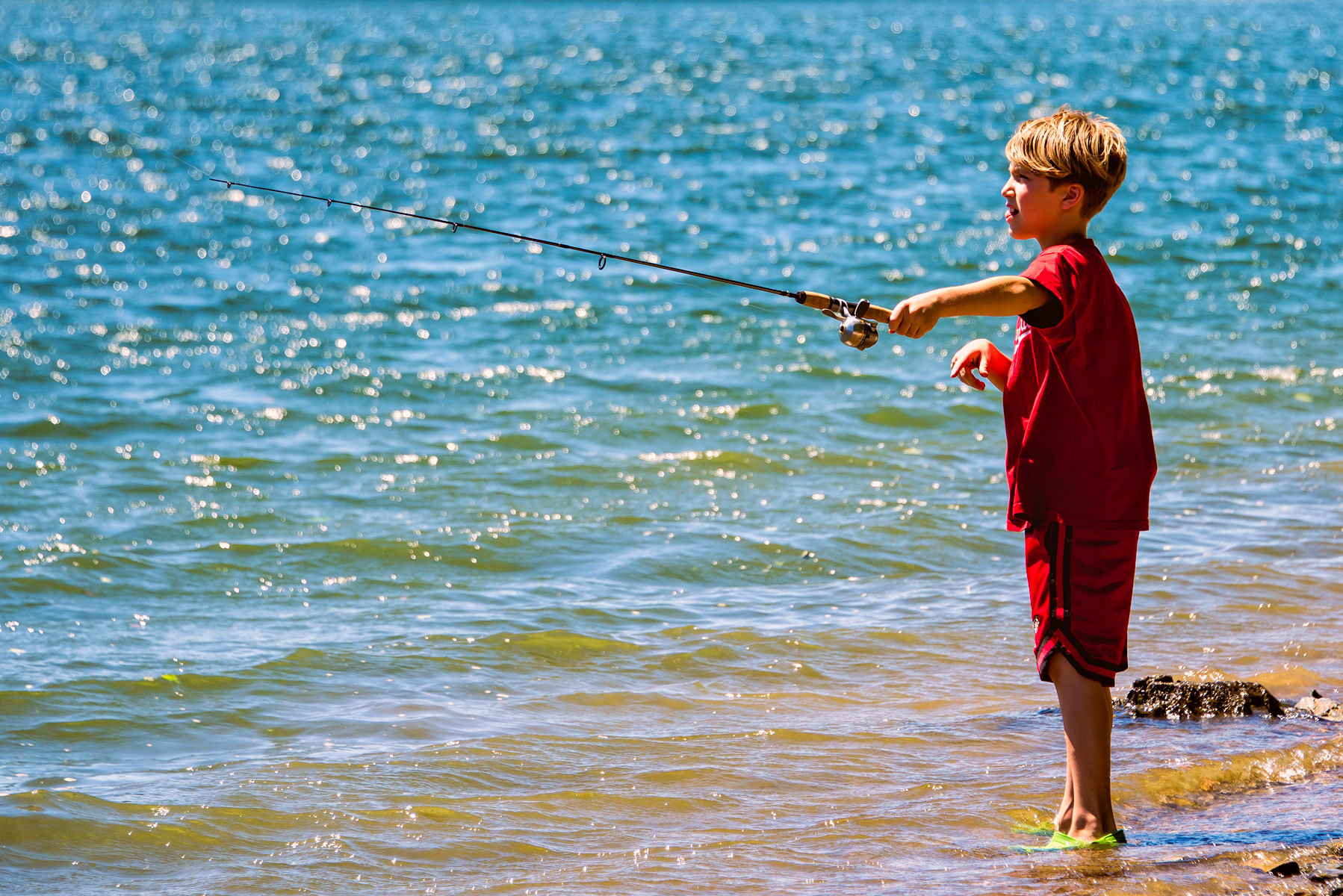 Little boy in red fishing with fishing rod