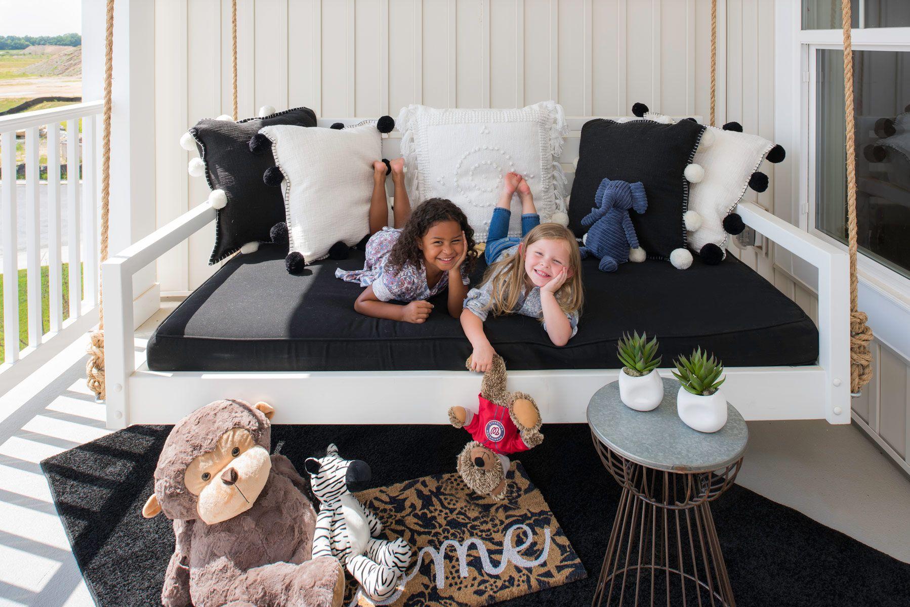 Little girls on porch swing holding teddy bear