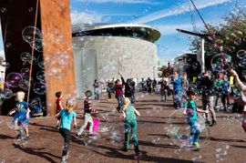 Kids blowing soap bubbles outside a museum in Amsterdam  joy