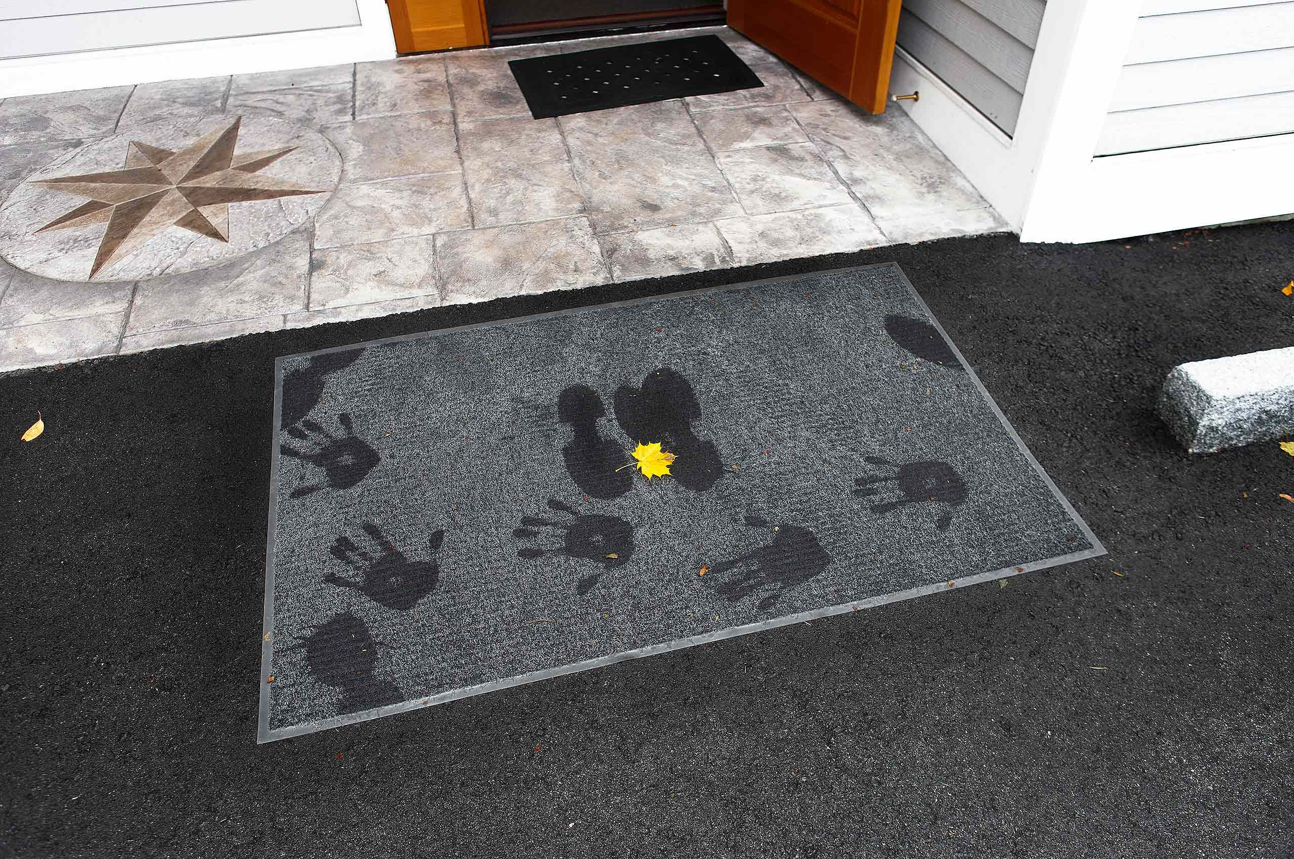 Footprints and handprints on doormat at Warren Roos Photo studio on South Portland Maine compass rose in background