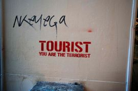 Graffiti stencil of Tourist you are the terrorist in Barcelona Spain