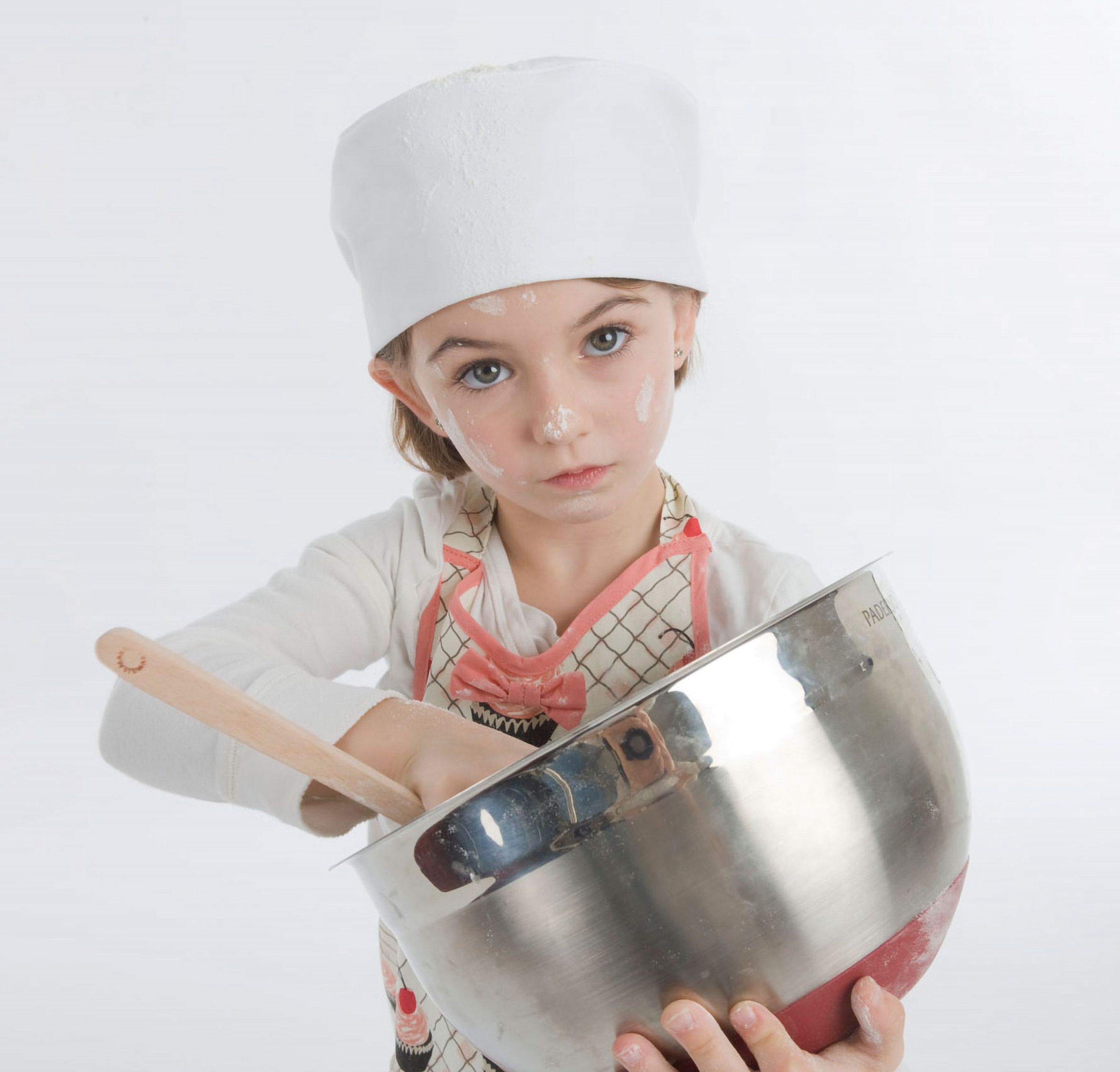 Commercial studio advertising photoshoot young girl chef and a bowl of frosting