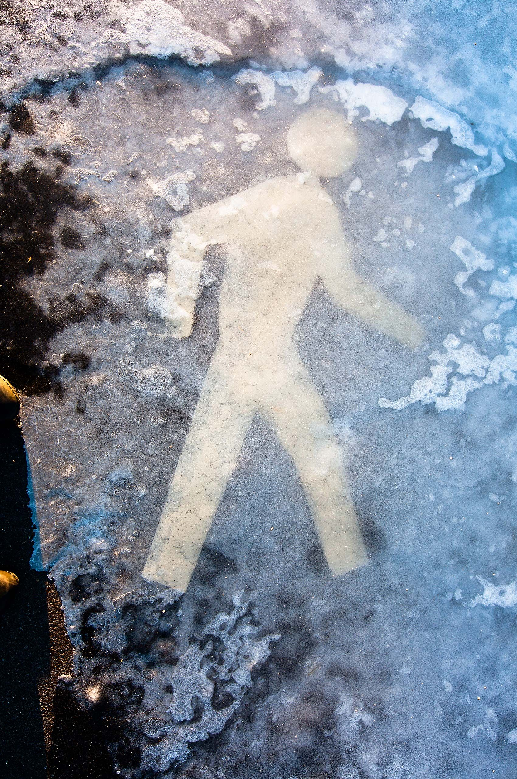 Pedestrian crossing icon man frozen in ice in winter in Manchester new Hampshire