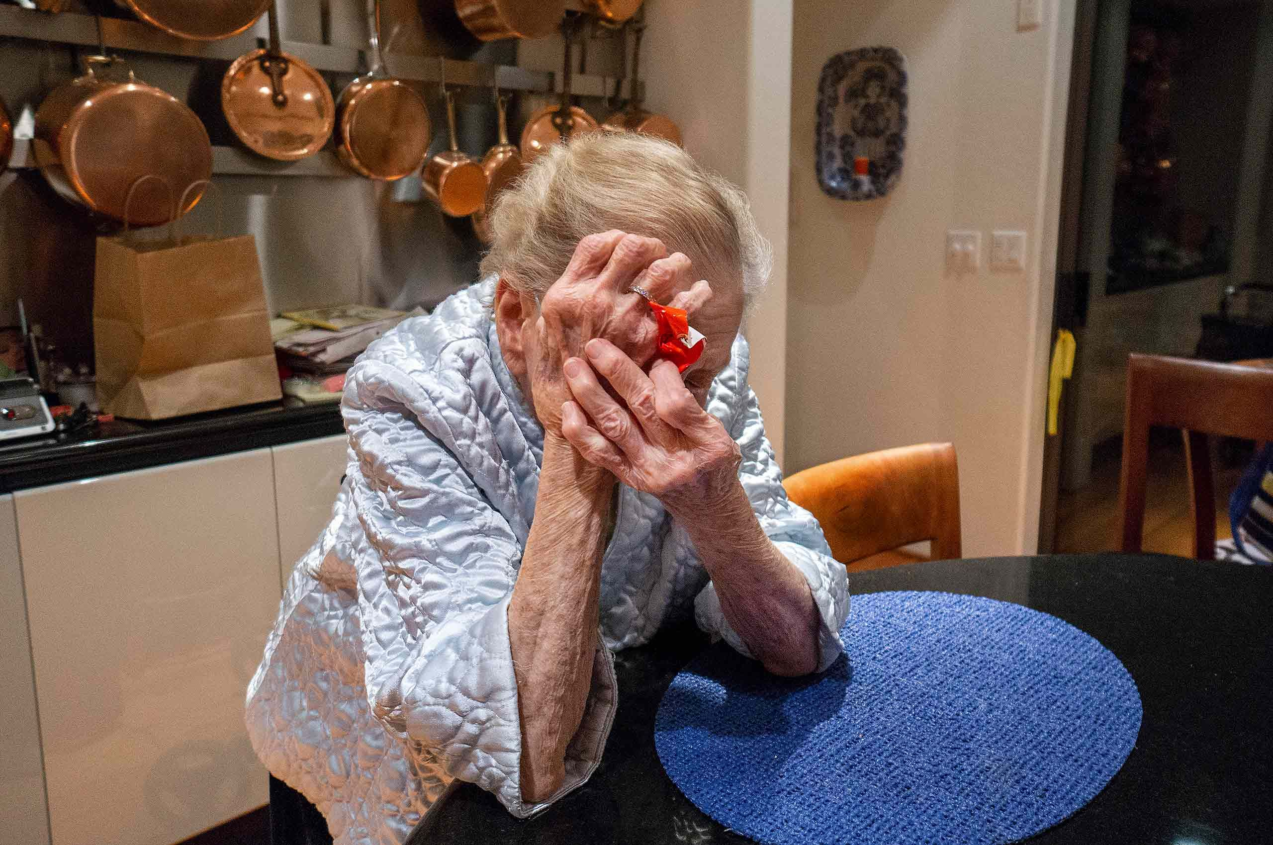 elderly woman hiding from camera copper pots lkitchen