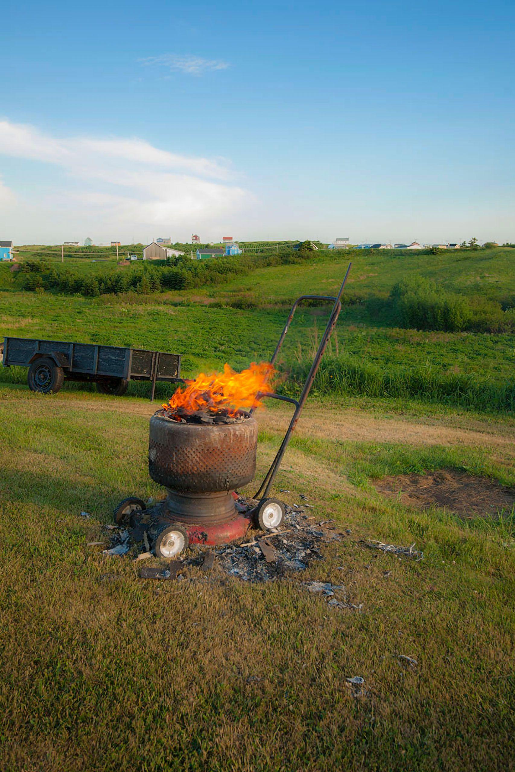 fire in a wash tub on a lawn mower Magdalen Islands Îles de la Madeleine Quebec Canada  Harve Aubert