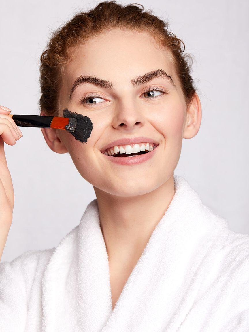model-applies-black-face-mask-with-brush.jpg