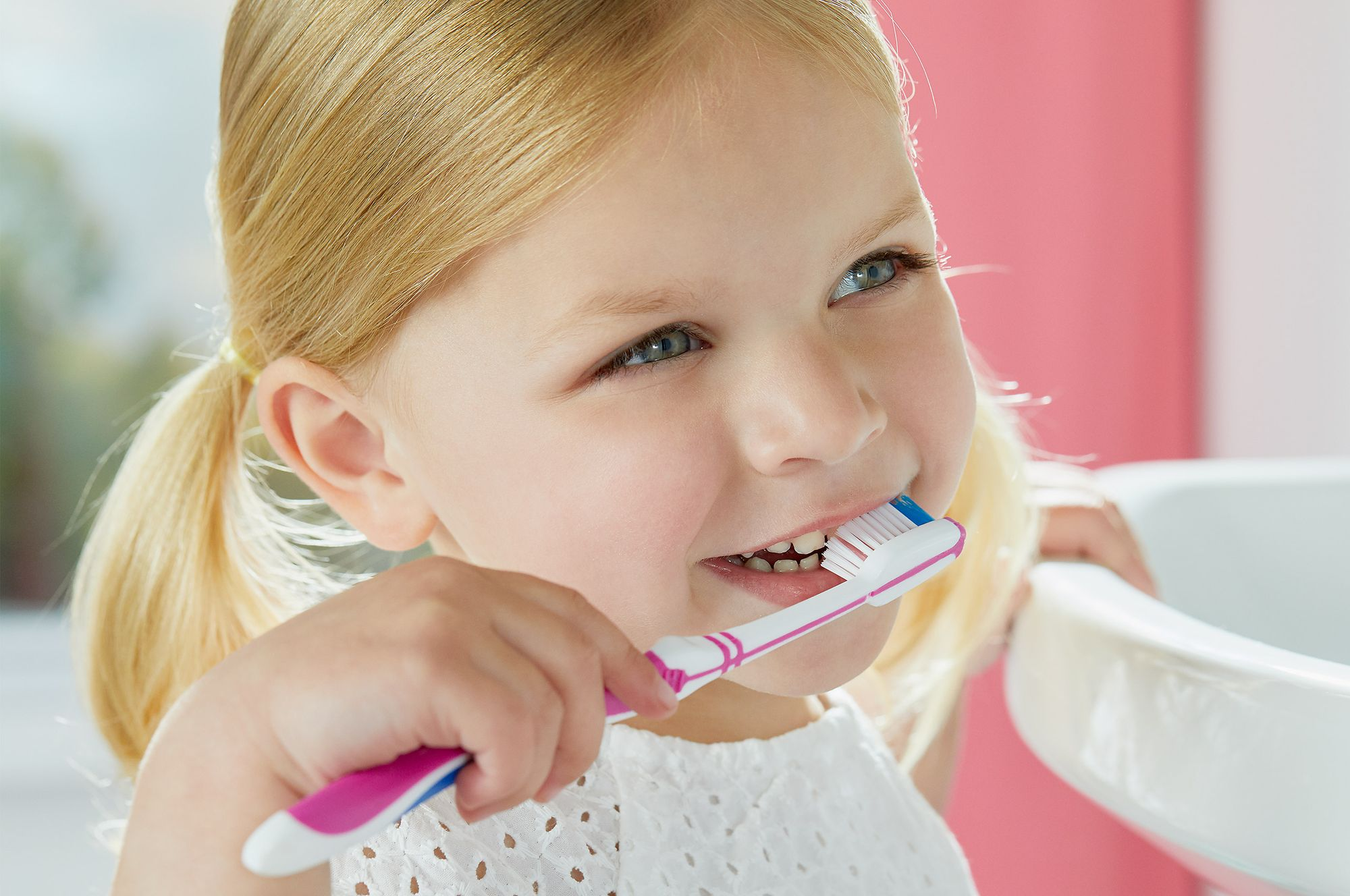 Caucasian young girl brushing her teeth