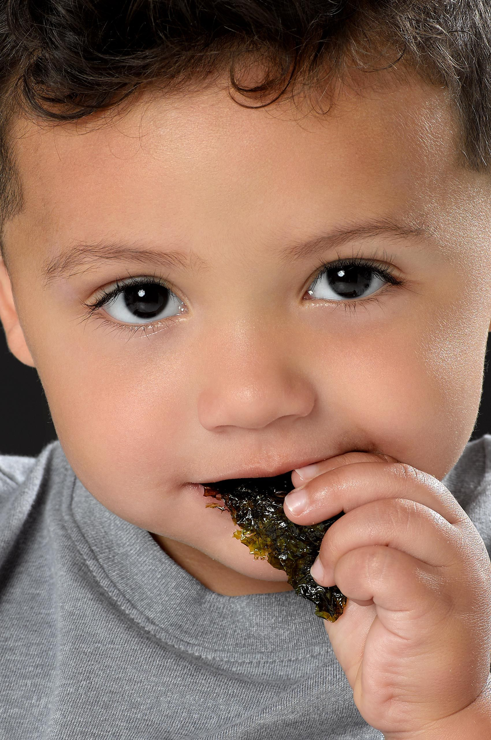 Young boy eating seaweed