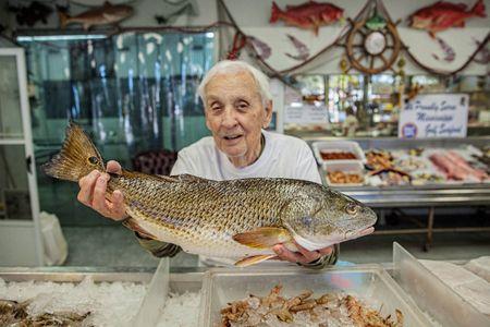 Man Holding Fish at a Fish MArket