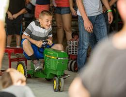 Kid Racing a Toy John Deere Tractor