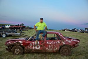 Man Sitting on His Car at a Demolition Derby