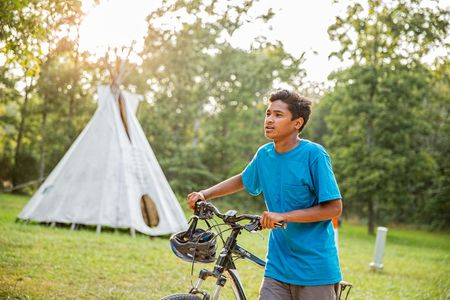 Boy Walking Bike IN Front of Teepee