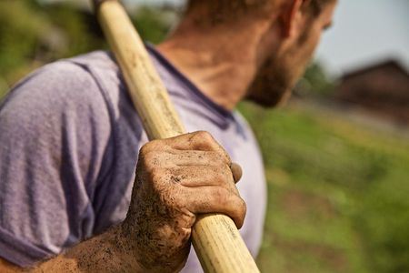 Male Farmer Looking at Farm Holding Hoe