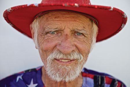 Head Shot of Man Smiling Dressed In Red White & Blue Colors