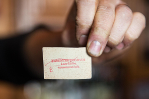 Man Holding an Old Card Relating to Absinthe