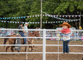 Young Boy Standing On Fence At a ROdeo