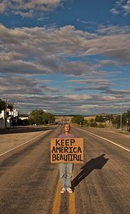 Woman Holding Keep America Beautiful Sign in the Middle of the Road