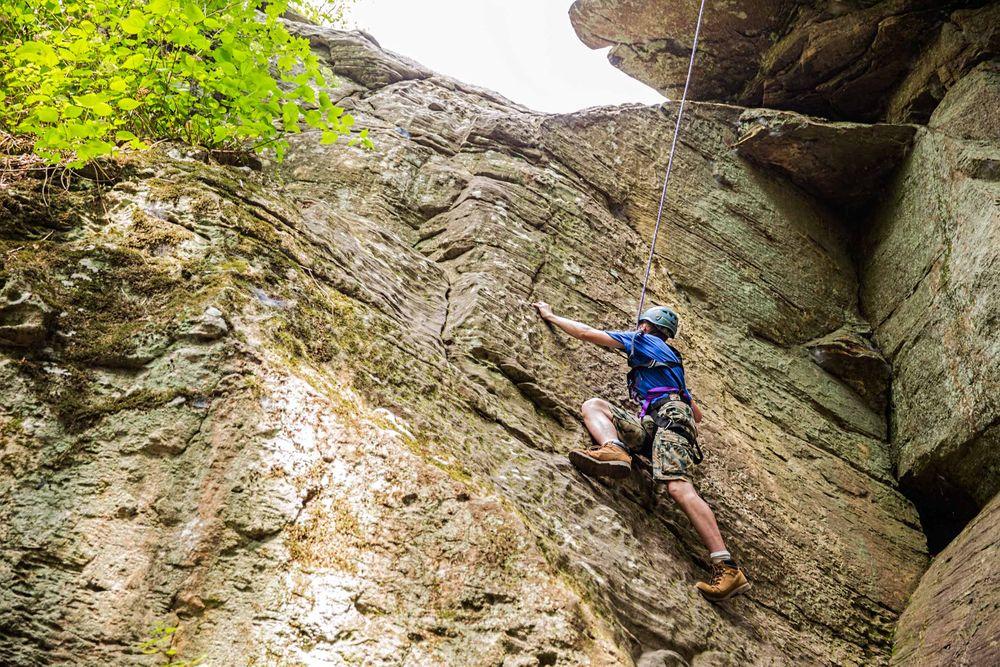Boy Climbing a Cliff
