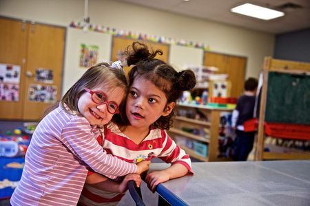 Two Young Girls Hugging in School