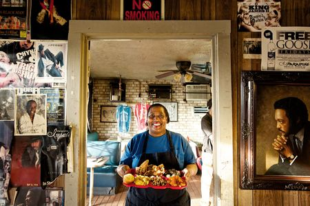 Woman Holding a Platter of Food in Bully's Restaurant