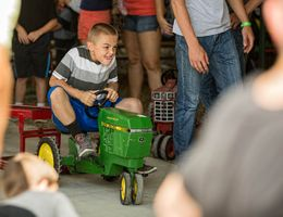 Kid Racing a Toy John Deere Tractor