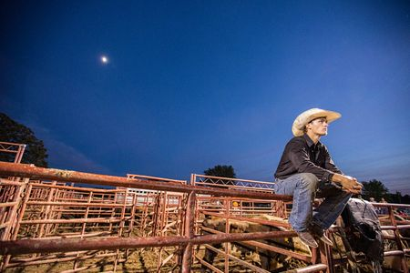 Cowboy Sitting On a Fence at Night Under the Moon