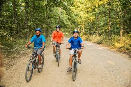 Three Boys Riding Bikes on a Dirt Road.