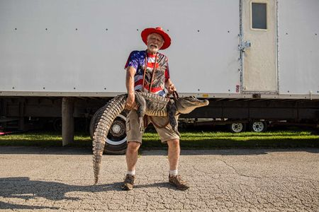 Man Dressed in Red White & Blue Holding an Alligator