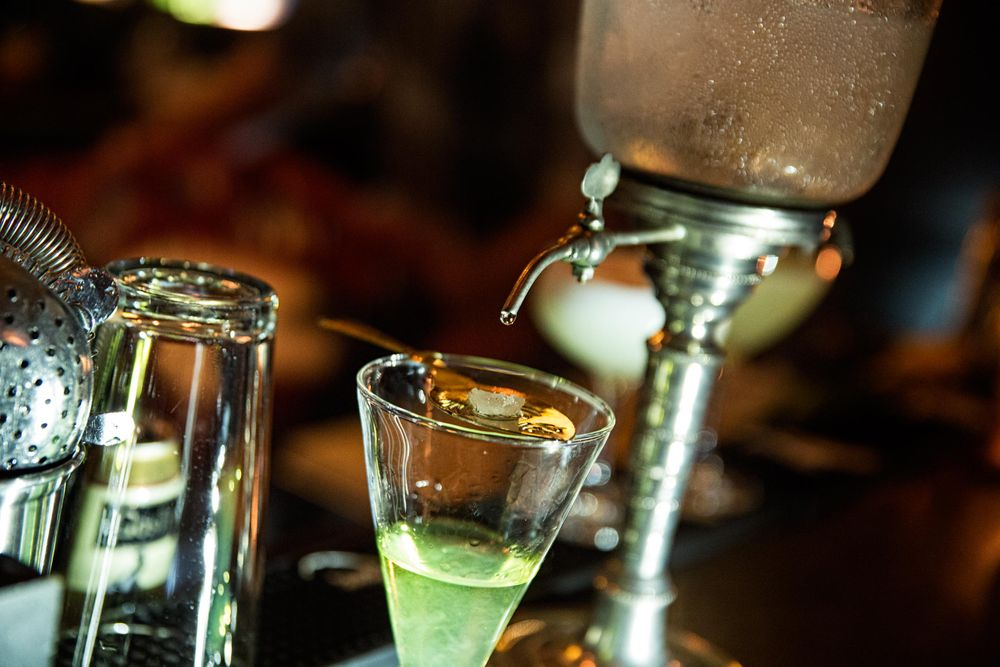 Tight Shot of Water Dripping into a Glass of Absinthe