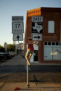 Boy Hangs On a Road Sign
