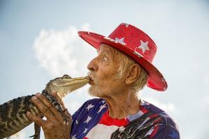 Man Kissing a Baby Aligator