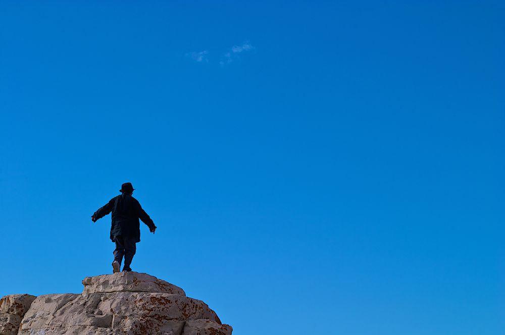 Man In a Suit On Top Of  a Cliff