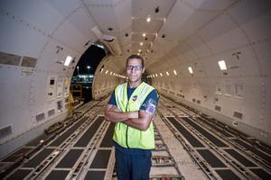 Worker Standing inside an Empty Boeing 747 Cargo Plane