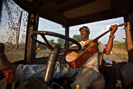 Rufas Roach Strumming Guitar In a Tractor