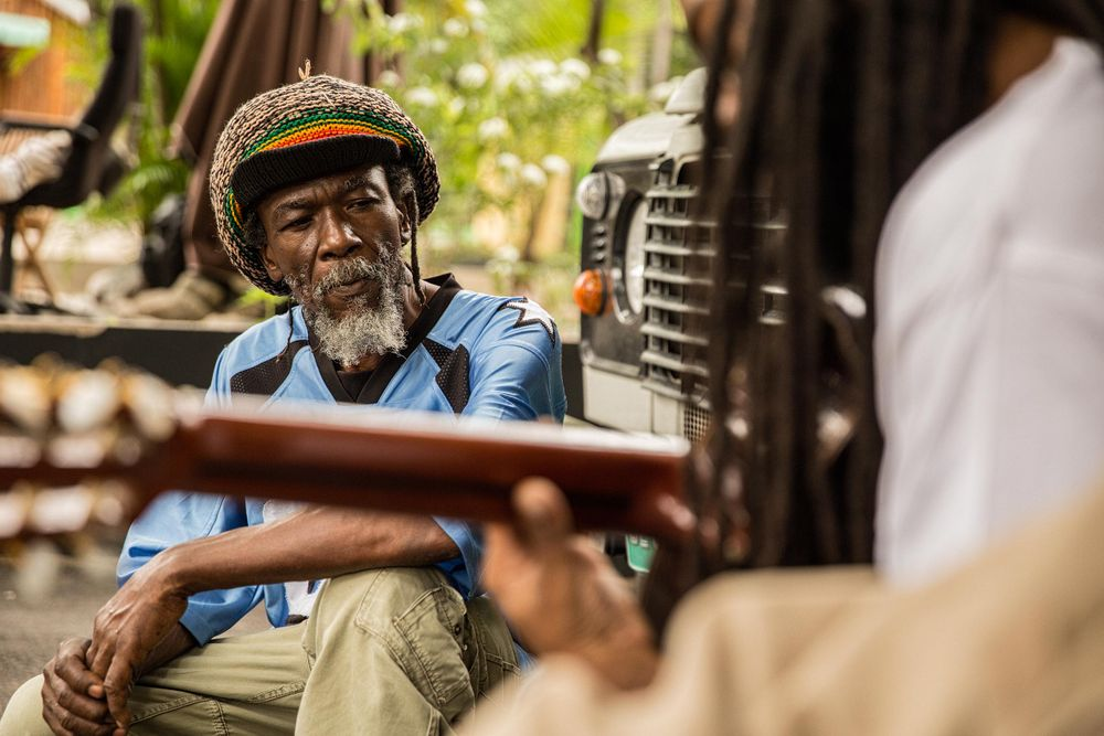 Rastafari Man Listening to a Man Playing Guitar